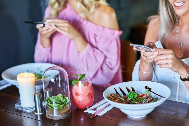 Two girl friends eating lunch in restaurant and using smartphone. Picture of two girl friends eating lunch in restaurant royalty free stock images