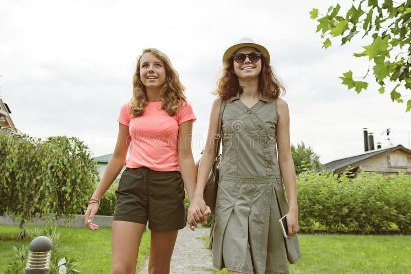 Two girl friends go holding hands, background lawn path near the house. royalty free stock photos