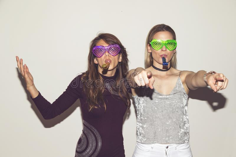 Girls clubbing. Two girl friends having fun, dancing and making crazy faces while taking photos at a party royalty free stock photo