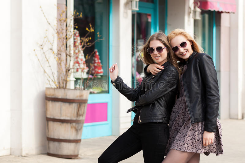 Two girl friends having fun outside in the city. Friendship and urban lifestyle stock image