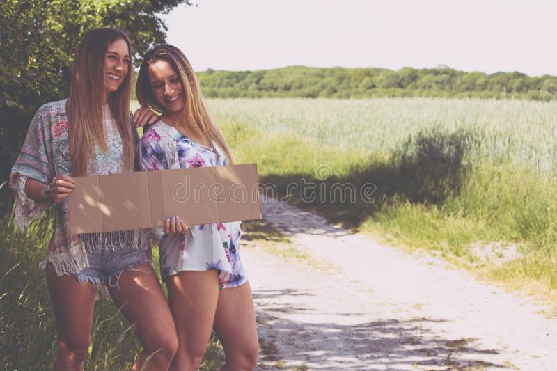 Two girl friends waiting with a paper plate to hitchhiking royalty free stock image