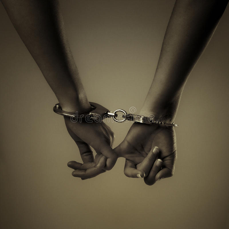 Two girl hand and handcuffs stock image