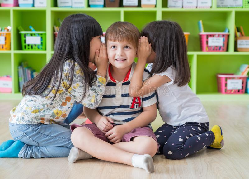 Two girl kids whisper secret at ear of boy in library at kindergarten preschool,Fun and happy children,back to school concept stock images