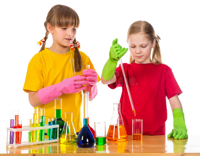 Two girl making a chemical experiment. Standing on the table with scientific equipment, isolated on white royalty free stock photography