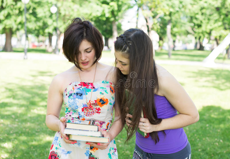 Two girl student reading. Two girls students studying subjects in the park stock images