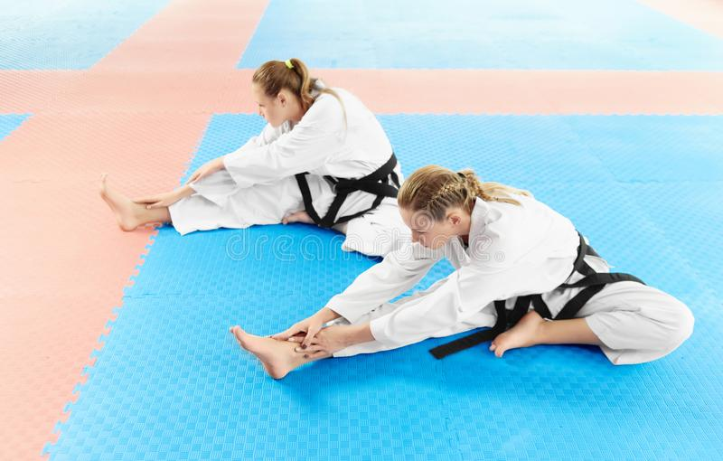 Two girl wearing in kimono and black belts, training their flexibility. stock image