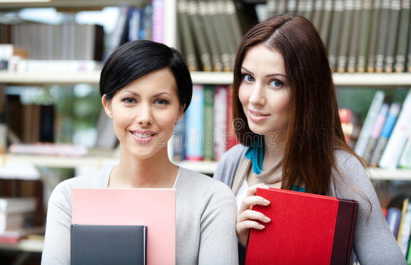 Two girlfriends with books stock image