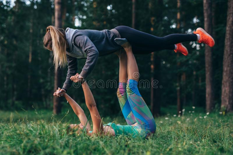 Two girlfriends doing partner yoga pose, flying warrior, on grass in forest stock photography