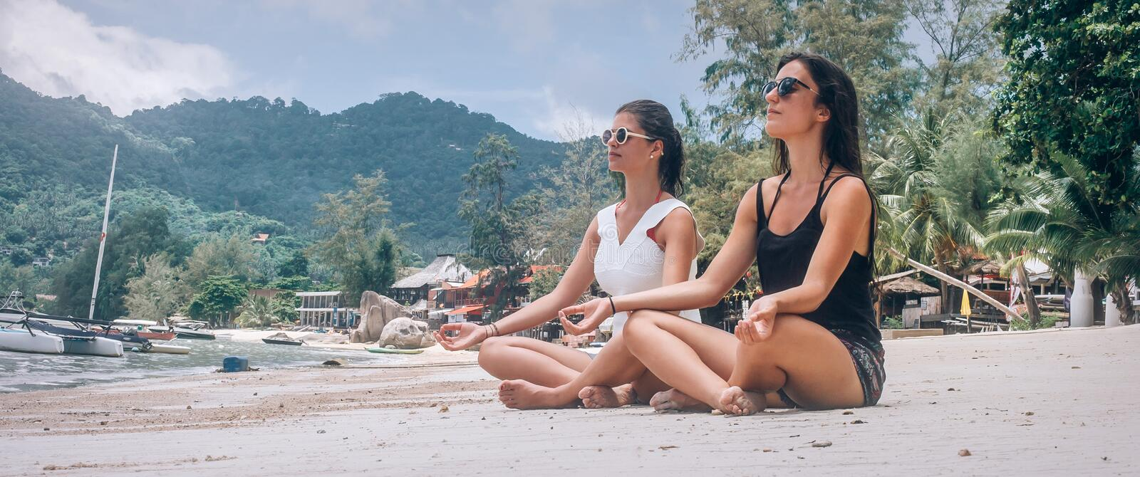 Two girlfriends doing yoga pose on beach in lotus position. Two girlfriends doing yoga pose on beach in summertime in lotus position. Spiritually concept royalty free stock photos