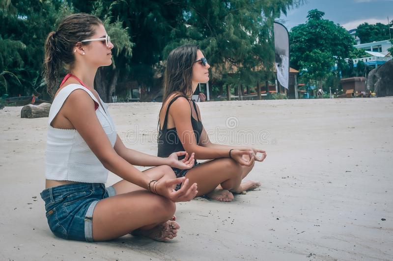 Two girlfriends doing yoga pose on beach in lotus position. Two girlfriends doing yoga pose on beach in summertime in lotus position. Spiritually concept stock photo