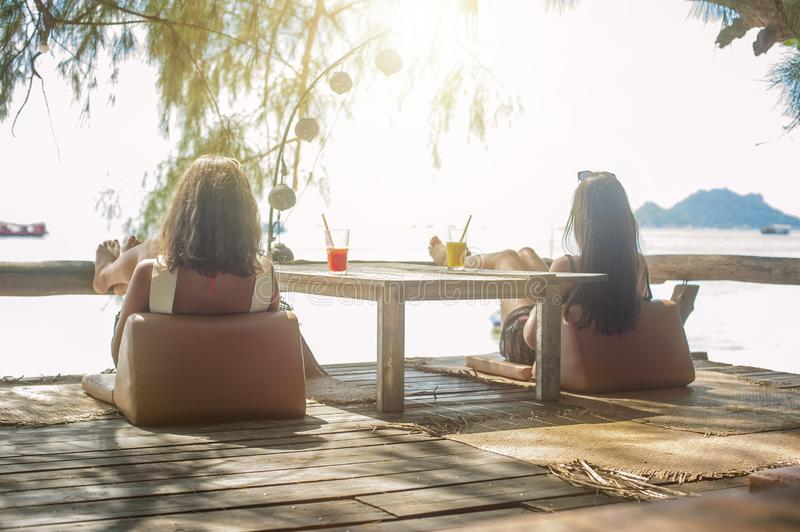 Two girlfriends drinking fruit cocktail on a tropical beach. Two girlfriends sitting in bar cafe, drinking fruit cocktail on a tropical beach stock photo