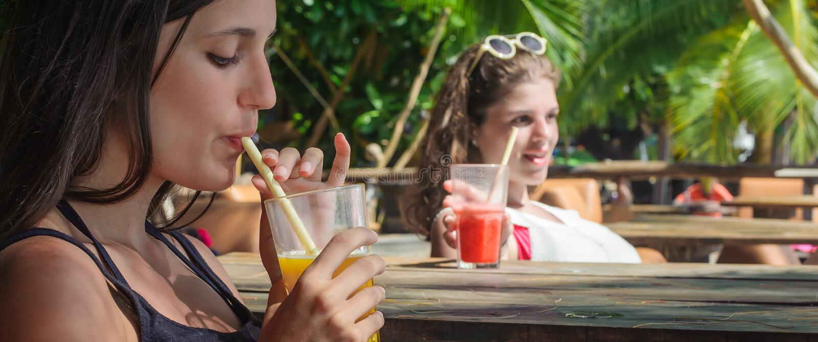 Two girlfriends drinking fruit cocktail on a tropical beach. Two girlfriends sitting in bar cafe, drinking fruit cocktail on a tropical beach royalty free stock photography