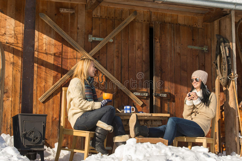 Two girlfriends enjoy tea winter snow cottage stock photography