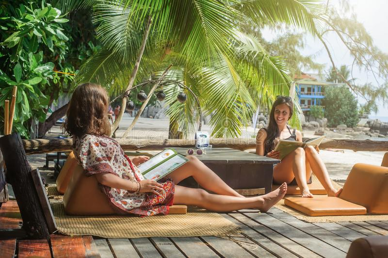 Two girlfriends enjoying tropical vacation sitting in bamboo beach bar. Cafe and looking at menu royalty free stock image
