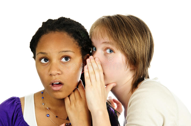 Two girlfriends gossiping. Isolated portrait of two diverse teenage girl friends gossiping royalty free stock photos