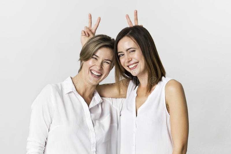 Two girlfriends having fun at studio background. Toothy smiling two young women portrait stock photography
