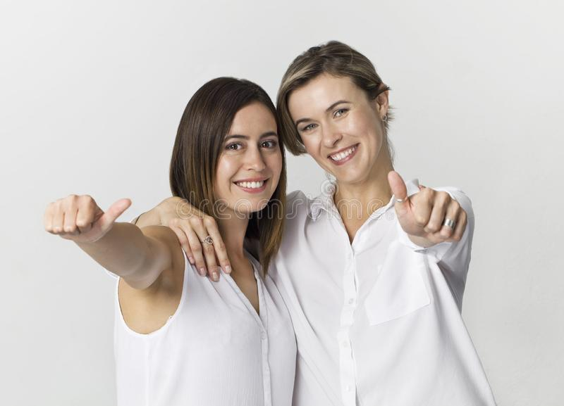 Two girlfriends having fun at studio background. Two young women smiling portrait stock photo