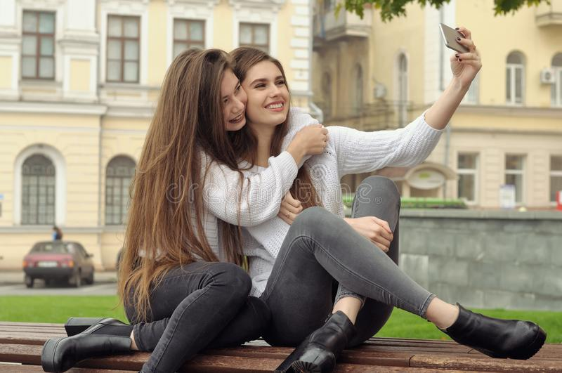 Two girlfriends hug and laugh as they make a selfie photo. They both have long brown hair that is long to the waist and they are dressed in identical white royalty free stock photos