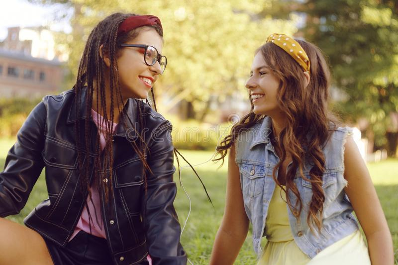 Two girlfriends listen to music together in the park. Sisters are dancing and having fun. Two girls are listening to music on royalty free stock photography