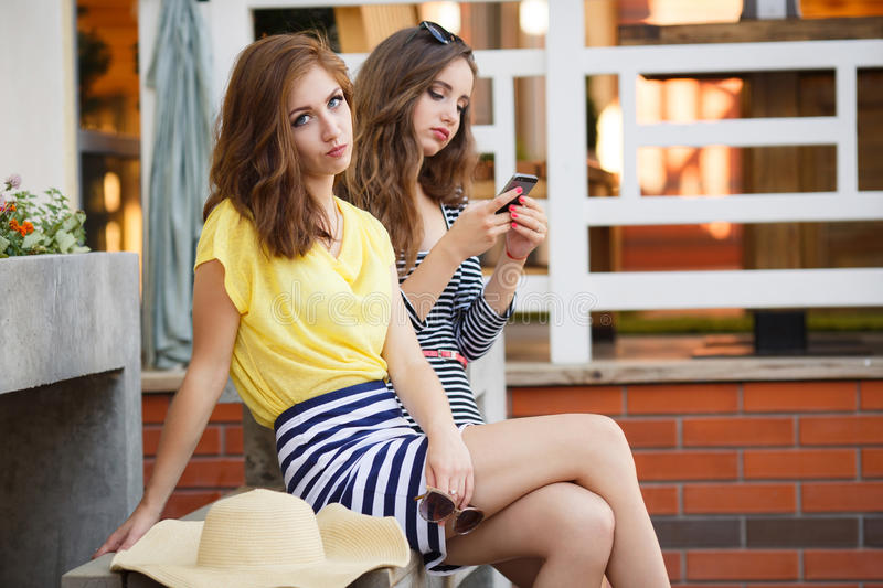 Two girlfriends looking photos on mobile phone. Two beautiful young women,brunettes with long hair,sitting on the bench near his home in the summer,consider and stock image
