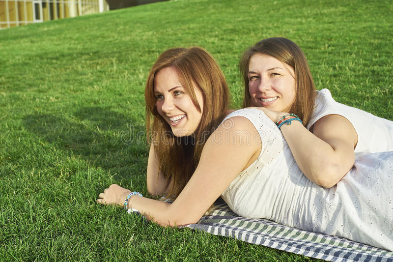 Two girlfriends lying on the lawn stock images