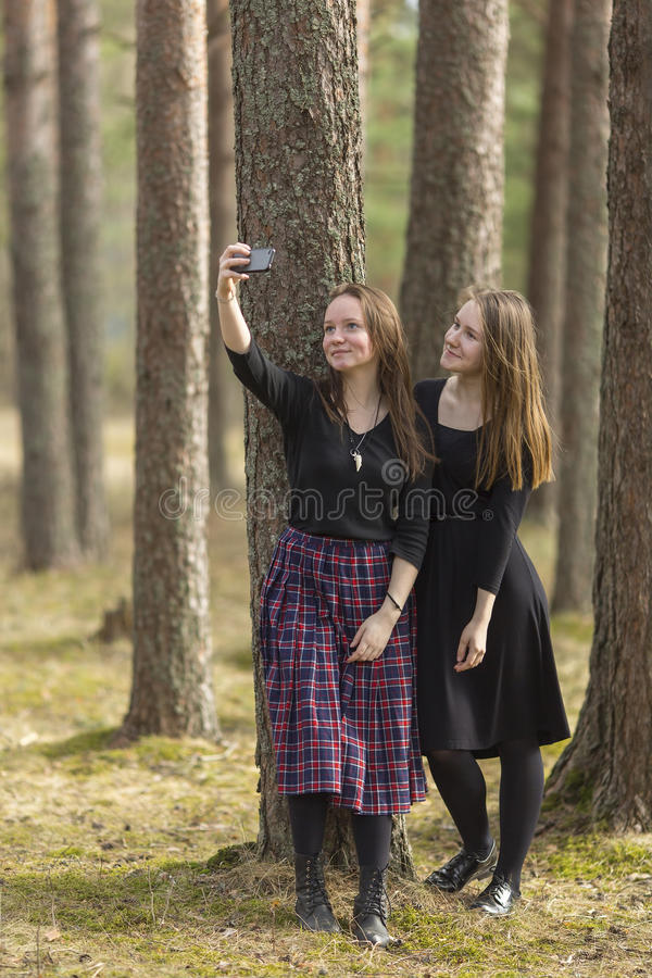 Two girlfriends make selfie photo on the smartphone while standing among the pines in the Park. Nature. royalty free stock images