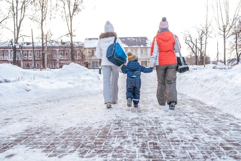 Two girlfriends mom escort small child boy 2-4 years. Women parents Hold hands, go in the winter in the city along the stock photos