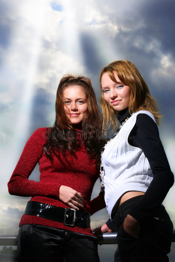 Two girlfriends over dramatic sky. Two girlfriends, sky with rays of light shining trough dramatic clouds behind them royalty free stock photos