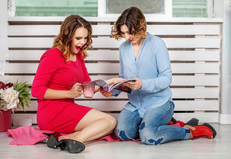 Two girlfriends read women`s magazine room. The concept of lifes royalty free stock images