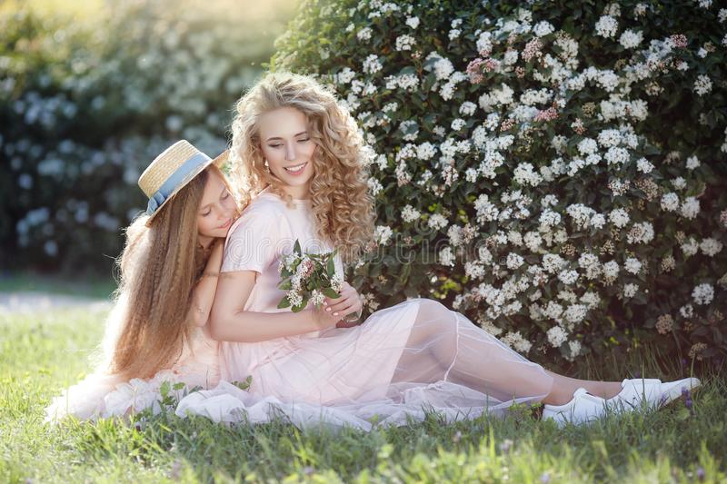 Two girlfriends run through the spring Park holding hands. Two cute teenage girls cheerfully spend time in the spring park. Two girlfriends running around the royalty free stock photo