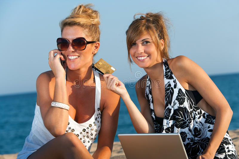 Two Girlfriends Shopping On Line At Beach. Stock Photo