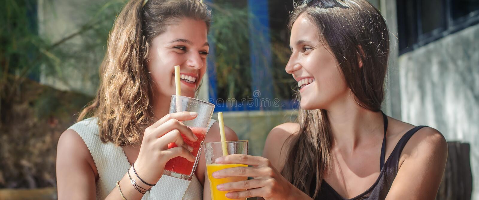 Two girlfriends drinking fruit cocktail on a tropical beach. Two girlfriends sitting in bar cafe, drinking fruit cocktail on a tropical beach stock image