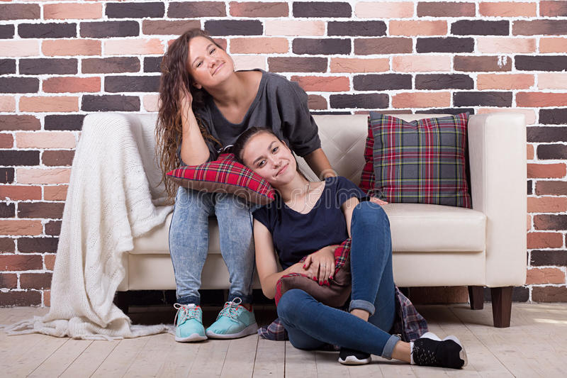 Two girlfriends sitting on the couch and smiling. Young beautiful girlfriends sitting on the couch and smiling stock photos