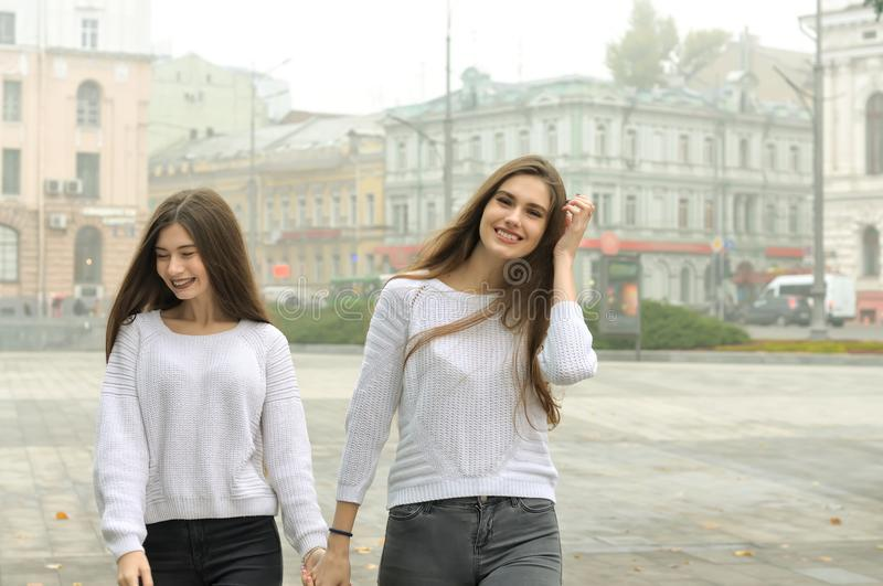 Two girlfriends are walking around the square holding hands royalty free stock image