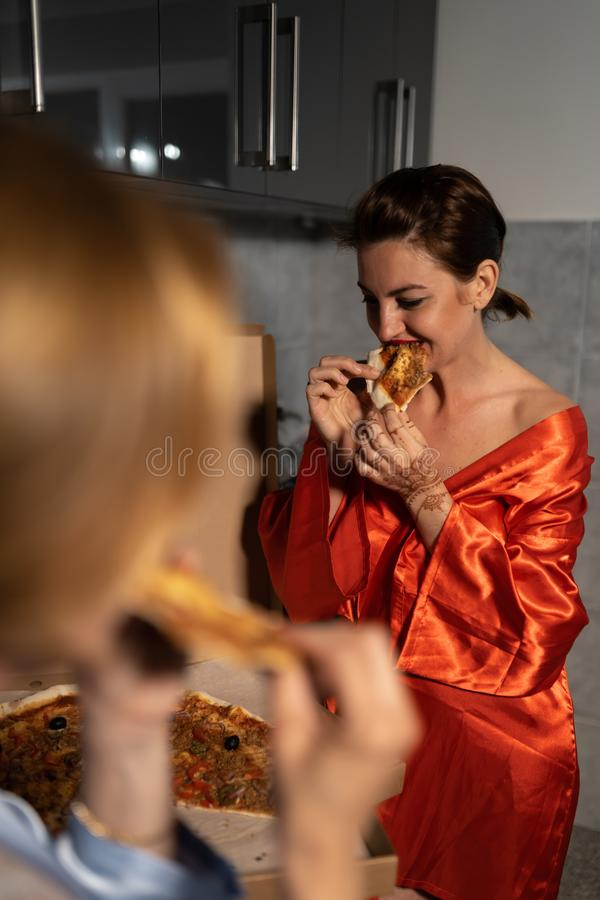 Two girlfriends women eating pizza and enjoying an evening party chat before going out - One wearing blue morning gown stock images