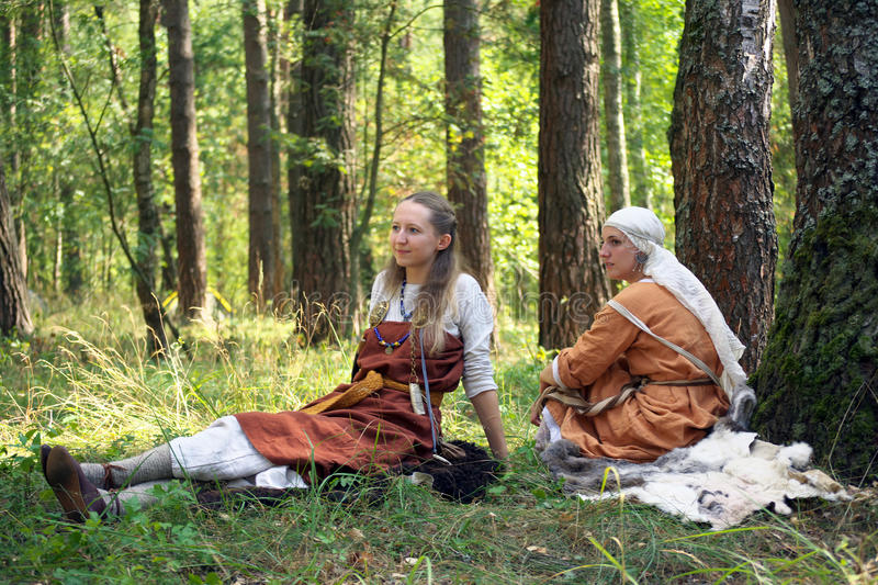 Two girls in the ancient Russian clothes sitting on the grass during the festival of historical reconstruction stock photography