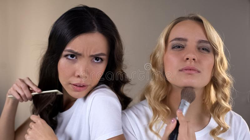 Two girls applying make up, fighting for place in front of mirror, rivalry, envy stock image
