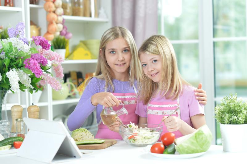 Two girls in aprons preparing fresh salad. On kitchen table with tablet royalty free stock photography