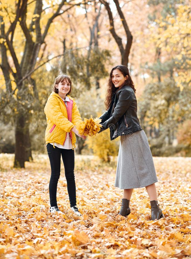 Two girls are in autumn city park. They pick leaves stock photography