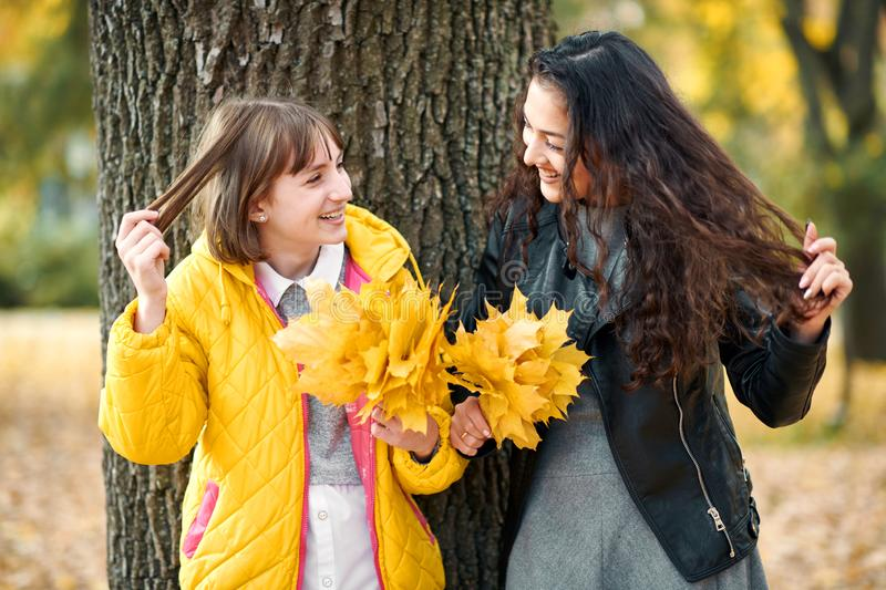 Two girls are in autumn city park. They stand near tree and show hair. stock image