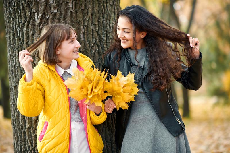 Two girls are in autumn city park. They stand near tree and show hair stock image