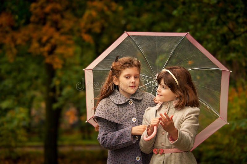 Two girls in autumn park stock photos