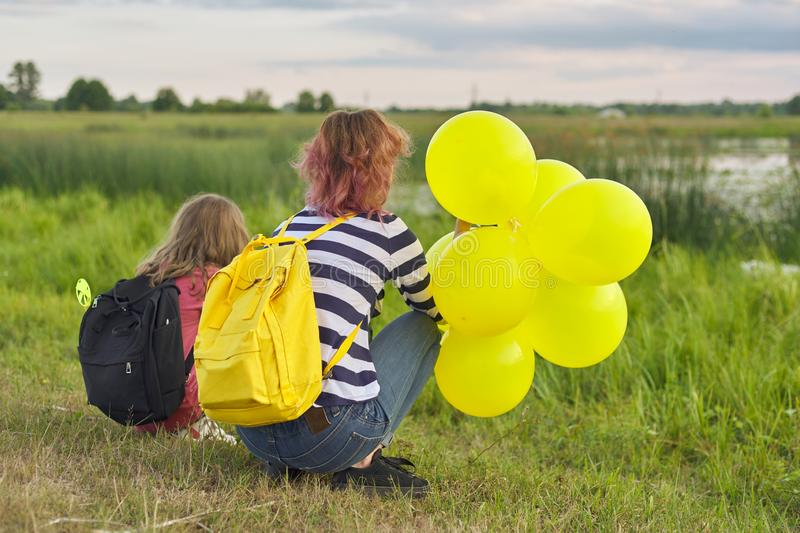 Two girls with balloons back in nature, children near the lake stock images