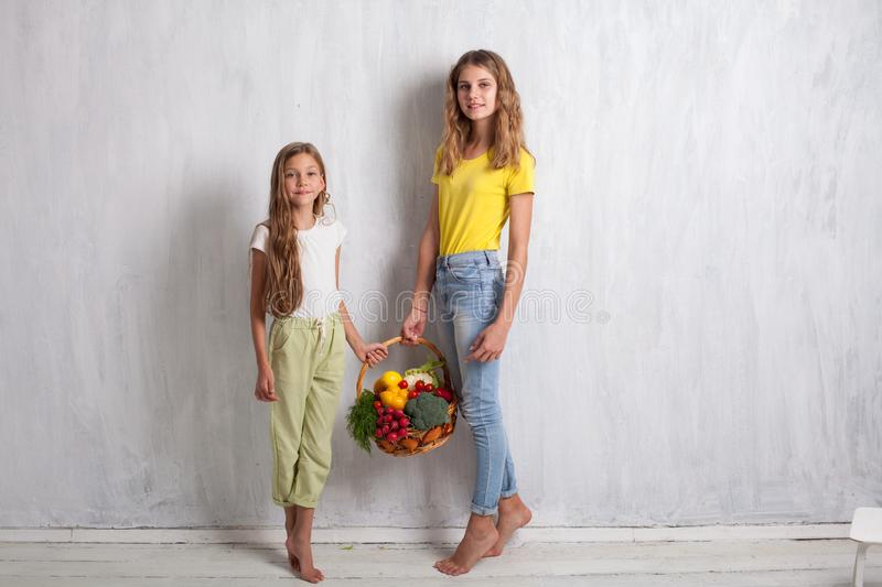 Two girls with a basket of fresh fruit healthy eating stock image