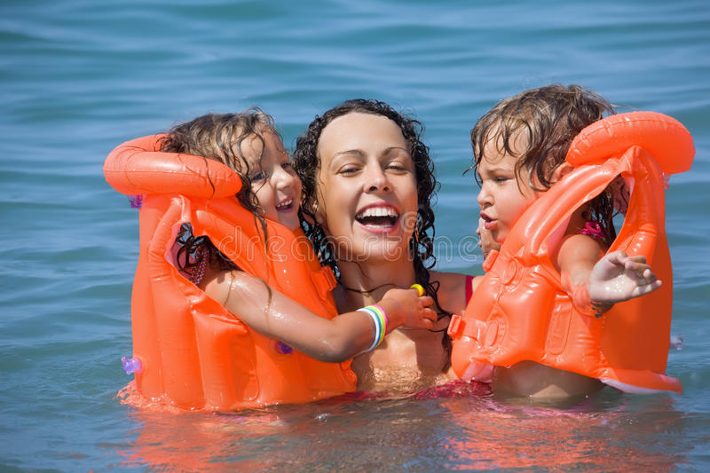 Two Girls Bathing In Lifejackets With Young Woman Stock Photography