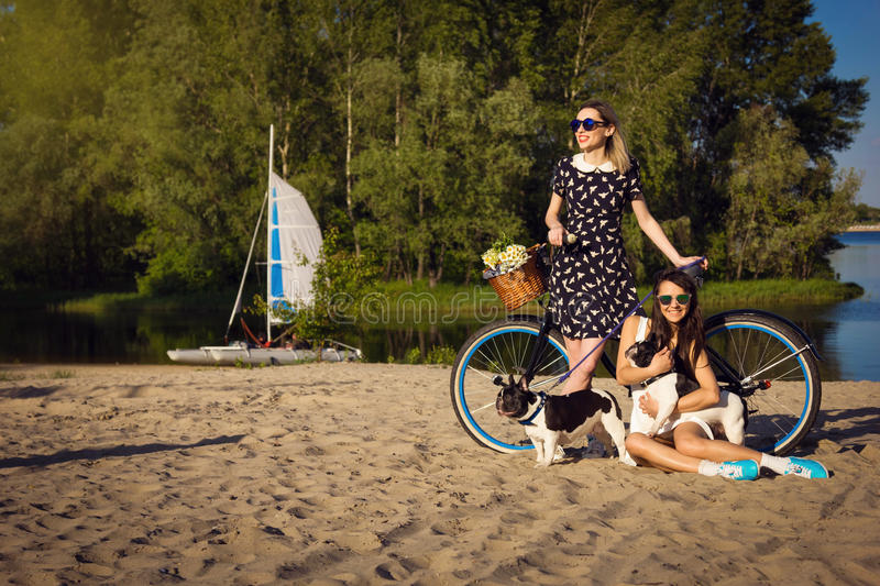 Two girls on the beach with bicycle and french bulldogs royalty free stock images