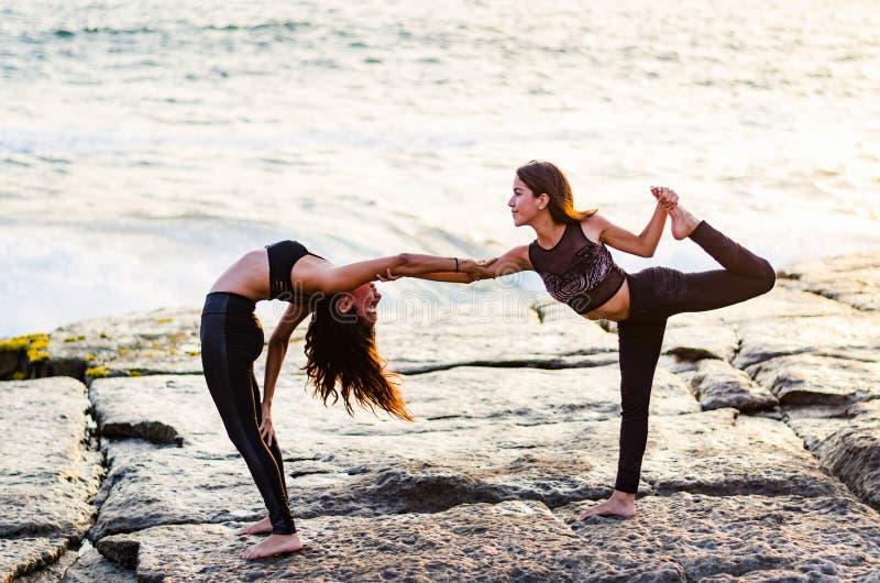Two girls on the beach doing yoga at sunset. Lima Peru. stock photo