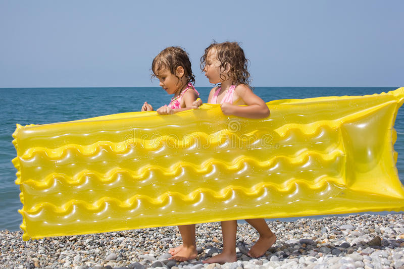 Two girls bearing in hands inflatable mattress stock images