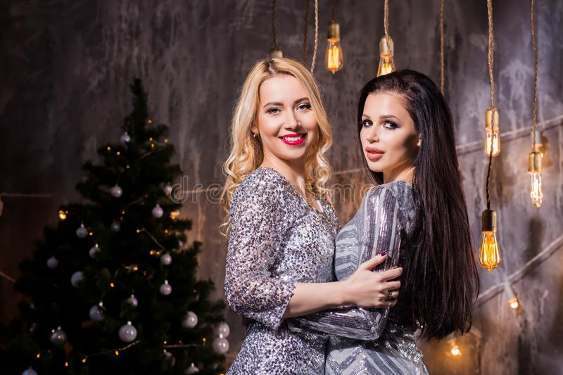 Two girls in a beautiful dress dancing and smiling with a sparkl. Two beautiful brunette and blonde women in silver sparkly dresses for the Christmas tree and stock image