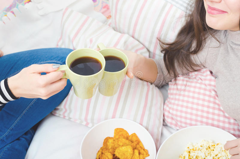 Two girls on bed drinking talking, drinking coffee, eating snacks stock photos